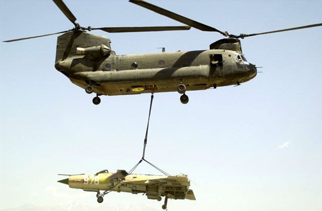 An Afghan MIG-21 wreck is lifted by CH-47D Chinook 86-01649 at Bagram Air Base, Afghanistan, circa 2002.