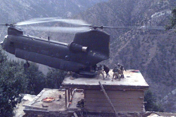 91-00264, a CH-47D, lands on the roof of a house in Afghanistan to pick up suspects during Operation Mountain Resolve, approximately November 2003.