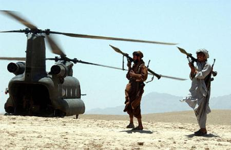 Local Afghan gunmen holding rocket propelled grenades (RPG) guard an American Chinook helicopter.