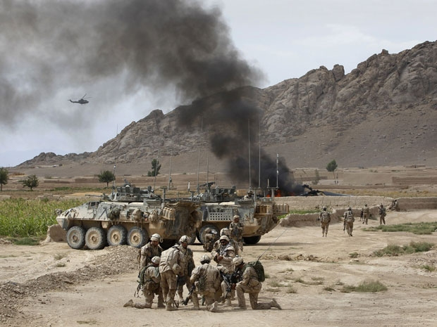 Canadian soldiers gather near a burning Canadian Forces CH-147 Chinook helicopter after it made a hard landing close to the village of Bazaar e Panjway, in the Panjway district west of Kandahar on 5 August 2010.
