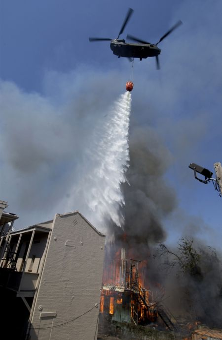6 September 2005: The crew of a CH-47 Chinook helicopter uses a water basket to drop water on two house fires in downtown New Orleans, Louisianna. The Chinook was part of a joint military and civilian effort to assist firefighters on the ground fighting the blazing house fires.