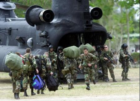 Members of the U.S. Special Forces and their Filipino counterparts board a U.S. Army MH-47E in the Philippines.