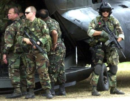 Two U.S. Special Forces stand guard with their firearms as other members board a U.S. MH-47E in the Philippines.